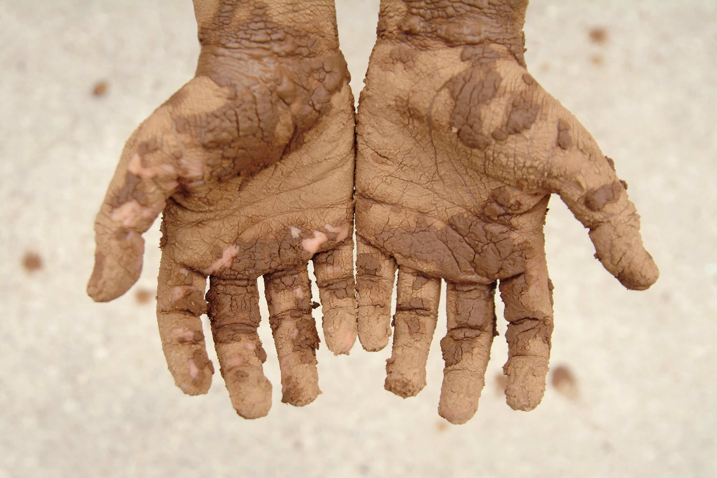 Outstretched hands covered in mud. Photo: iStock / Stephanie Phillips.